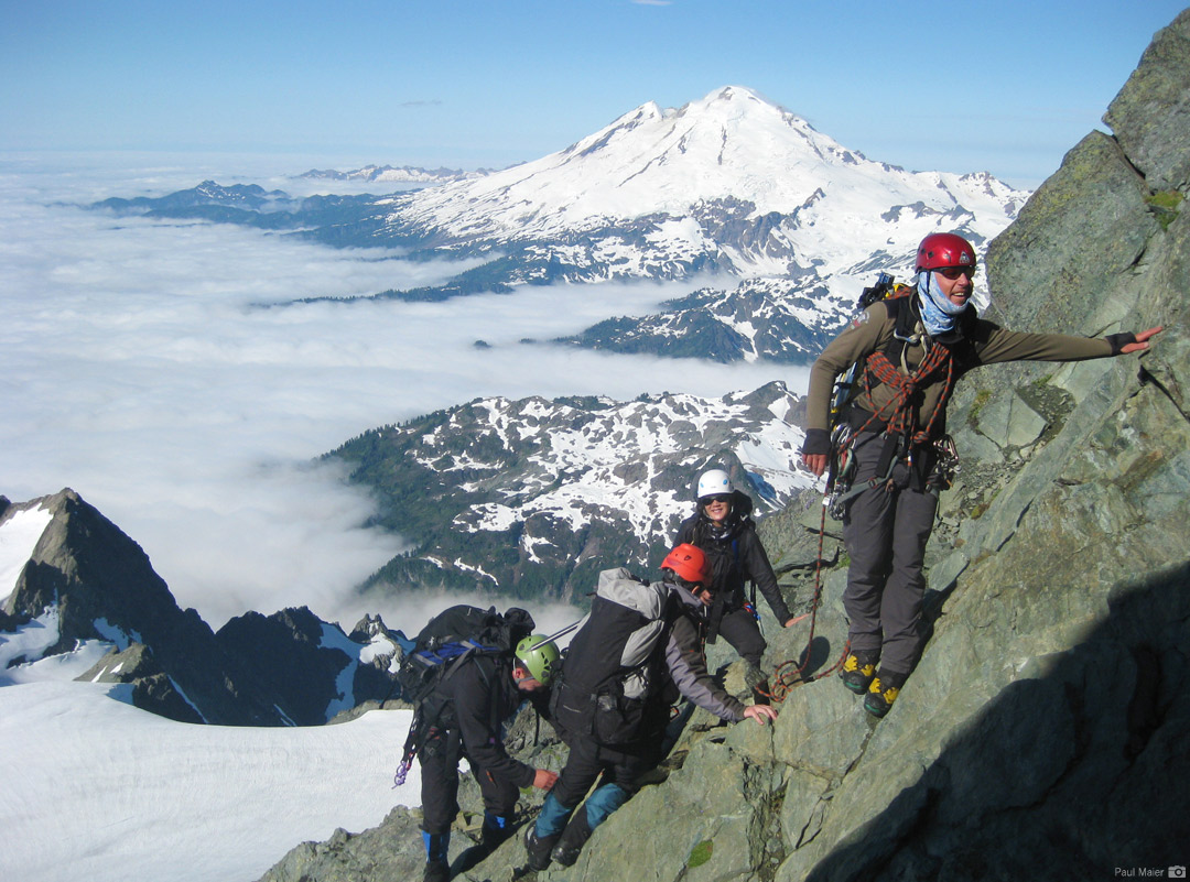 An RMI Team on Mt. Shuksan's Summit Pyramid with Mt. Baker in the distance