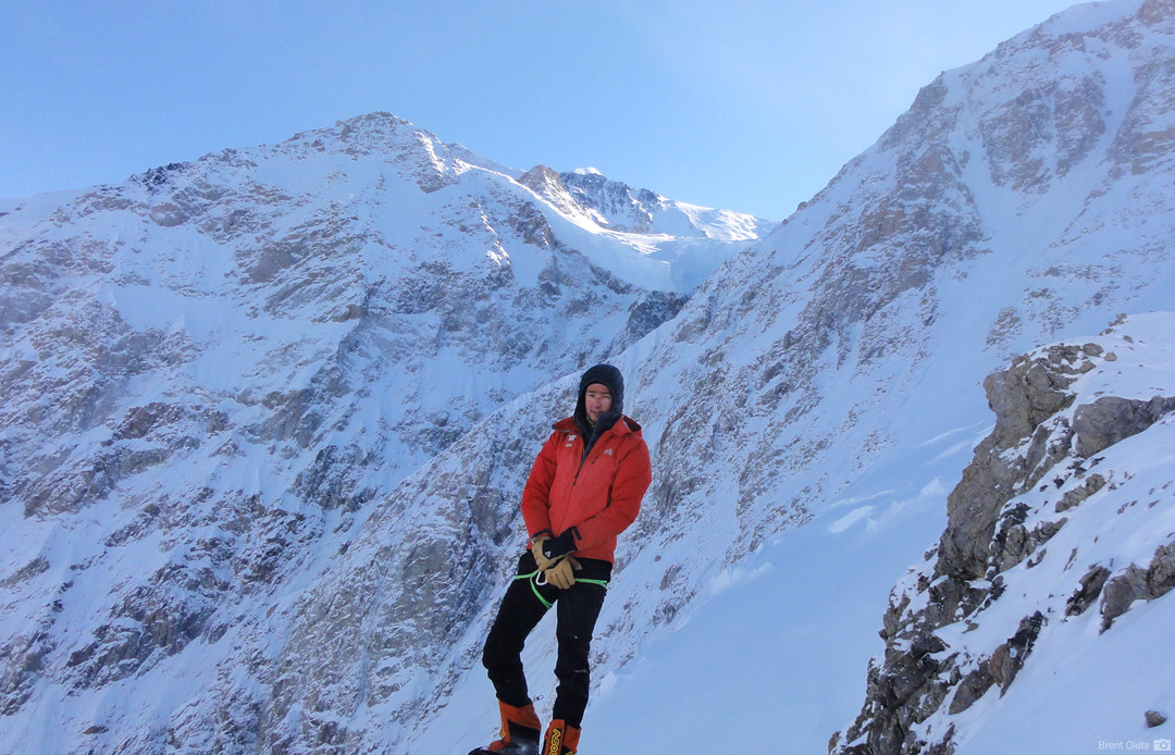 RMI Guide Leon Davis standing in front of the Father and Son's Wall on Denali's Northwest Face