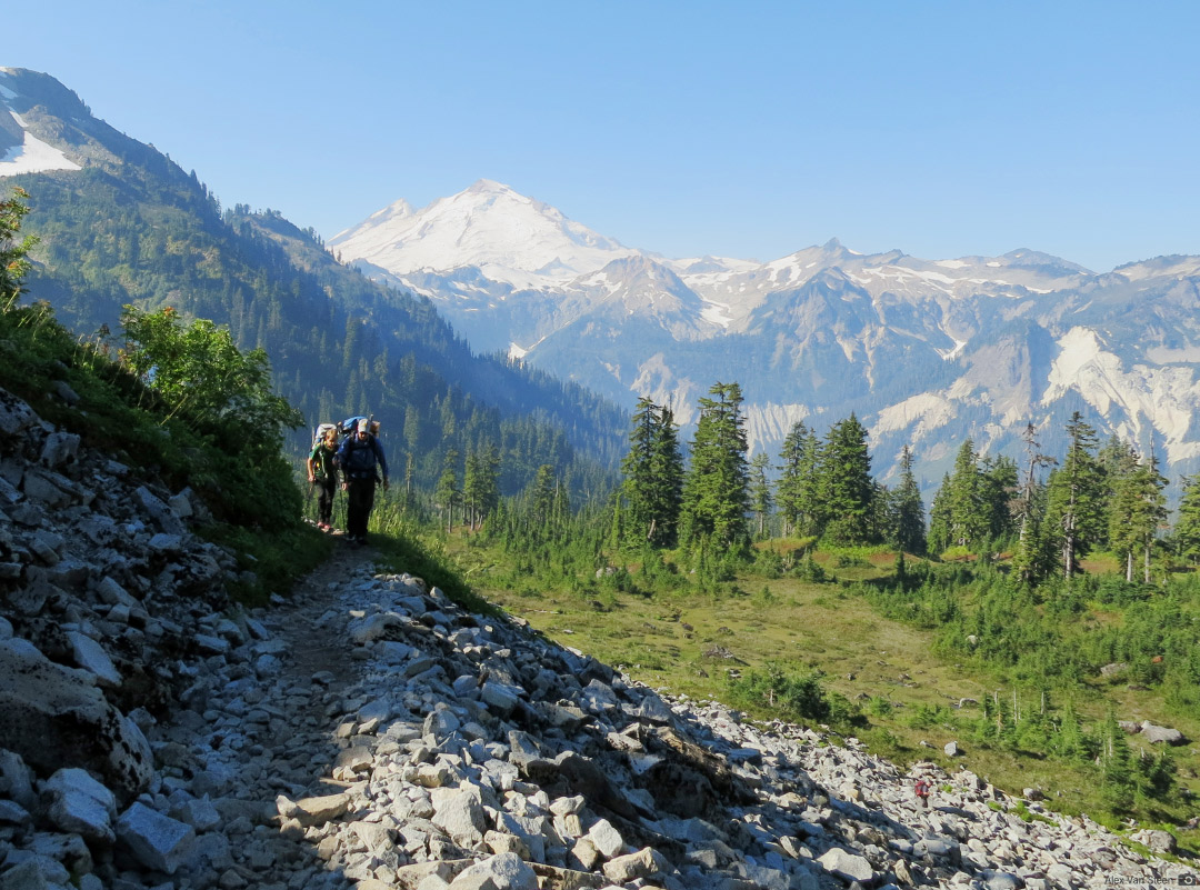 Approaching the base of Mt. Shuksan's Fisher Chimneys with Mt. Baker in the distance