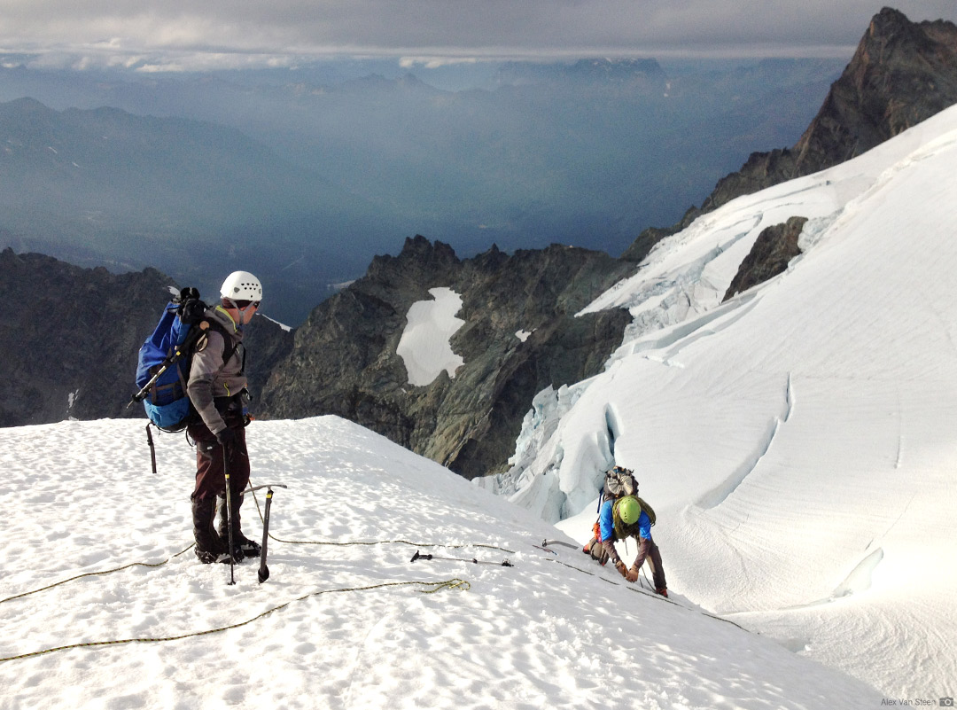 Descending the steep Upper Curtis Glacier with High Camp visible on the ridge behind